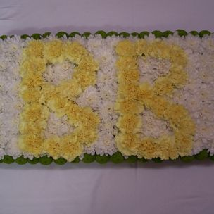 Yellow Letters on White based edged in foliage